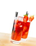 Two glasses of strawberry cocktail with ice on light wood table Royalty Free Stock Photo