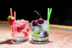 Two glasses of strawberry and grape mojitoes Stock Photos