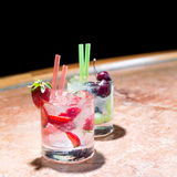 Two glasses of strawberry and grape mojitoes. On marble table Royalty Free Stock Image