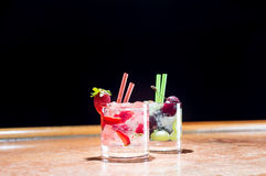 Two glasses of strawberry and grape mojitoes. On marble table Stock Photos