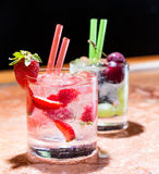 Two glasses of strawberry and grape mojitoes. On marble table Royalty Free Stock Photo