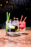 Two glasses of strawberry and grape mojitoes. On marble table Stock Images