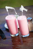 Two glasses with strawberry milkshake and straws Stock Image
