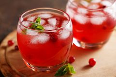 Two glasses of summer cold drink with cranberry juice, mint, ice cubes on the table. Homemade healthy berry beverage Stock Photo