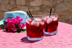 Two glasses of summer red cocktail with ice next to a blue hat and a sprig of Bougainvillea flowers on a pink table Royalty Free Stock Images