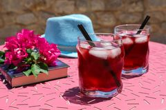 Two glasses of summer red cocktail with ice next to a book, a sprig of Bougainvillea flowers, blue hat on a pink table Stock Photography