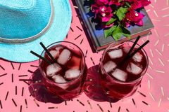 Two glasses of summer red cocktail with ice next to a book, a sprig of Bougainvillea flowers, blue hat on a pink table Royalty Free Stock Image