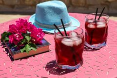 Two glasses of summer red cocktail with ice next to a book, a sprig of Bougainvillea flowers, blue hat on a pink table Stock Photo