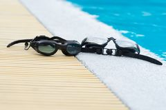 Two Glasses for swimming black on pool edge Stock Photo