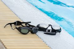 Two Glasses for swimming black on pool edge Royalty Free Stock Images
