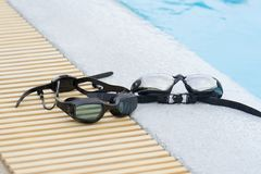 Two Glasses for swimming black on pool edge Royalty Free Stock Photography