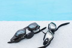 Two Glasses for swimming black on pool edge Stock Image