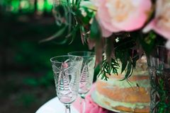Two glasses on the table on the background of flowers and cake. wedding ceremony. In the open air Stock Photography