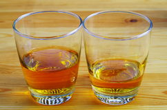 Two glasses of tea or whiskey  on a wooden table Stock Photos