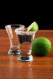 Two glasses of tequila, salt and lime Stock Images