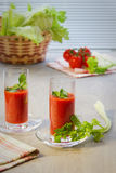 Two glasses with tomato juice, tomatoes, stalks and leaves of a celery on table. Two glasses with tomato juice, tomatoes, stalks and leaves of a celery on a royalty free stock photo