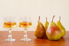 Two glasses of traditional bulgarian home made fruit brandy krushova rakia and four pears on a wooden table against light beige Stock Images