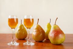 Two glasses of traditional bulgarian home made fruit brandy krushova rakia and four pears on a wooden table against light beige Royalty Free Stock Photo