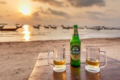 Two glasses of Chang beer on the beach at sunset