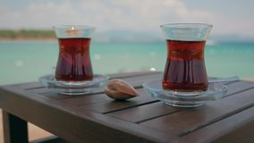 Two glasses of turkish tea on the table. With Mediterranean Sea on the background in Turkey. 4k. Other camera movements, raw flat color, frame rates, formats stock video
