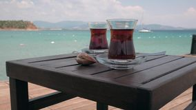 Two glasses of turkish tea on the table. With sailing yacht in the sea on the background. 4k. Other camera movements, raw flat color, frame rates, formats, and stock video footage