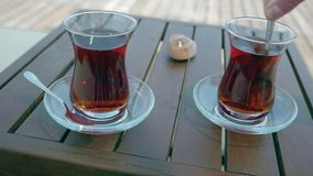 Two glasses of turkish tea on the table. With wooden table on the background in Turkey. 4k. Other camera movements, raw flat color, frame rates, formats, and stock video