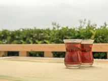 Two glasses of Turkish tea in traditional cup on wooden table. stock image