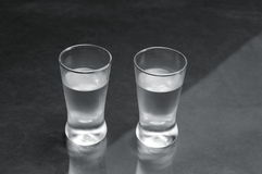 Two glasses of vodka on black marble table Royalty Free Stock Image