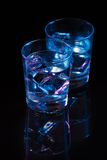 Two glasses of vodka with ice cubes against the background of deep blue glow. Two glasses of vodka with ice cubes against  the background of deep blue glow Royalty Free Stock Photo