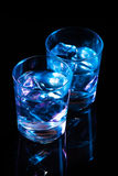 Two glasses with vodka and ice cubes against the background of deep blue glow on dark mirror Royalty Free Stock Photo