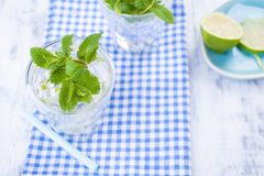 Two glasses of water and fresh green mint, and lime. On a blue napkin on a wooden background. free space for text or a postcard.  Royalty Free Stock Images