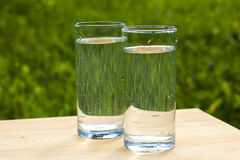 Two glasses of water on  grass background. Two glasses of сrystal clear water placed on a wooden surface on green grass background. Drops of water run down a Royalty Free Stock Image