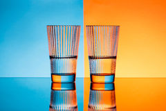 Two glasses with water over blue and orange background. Stock Images