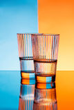 Two glasses with water over blue and orange background. Stock Photos