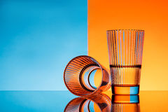 Two glasses with water over blue and orange background. Royalty Free Stock Images