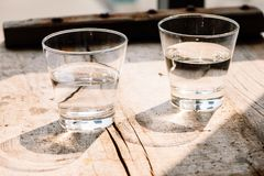Two glasses of water on table on wooden background.  Royalty Free Stock Photos