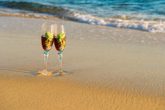Two glasses in a wave of the sea on the beach Stock Image