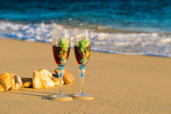 Two glasses in a wave of the sea on the beach Stock Photos