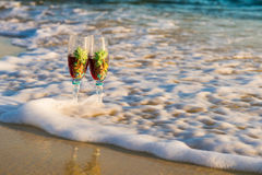 Two glasses in a wave of the sea on the beach Royalty Free Stock Photography