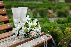 Two glasses and wedding bouquet on a bench Royalty Free Stock Photo
