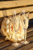 Two glasses and a wedding bouquet on wooden bench Royalty Free Stock Photography