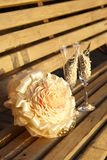 Two glasses and a wedding bouquet on wooden bench Royalty Free Stock Photos