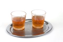 Two glasses of whiskey. On a silver tray on white background Royalty Free Stock Photo