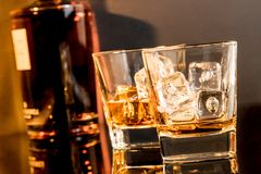 Two glasses of whiskey in front of whisky bottle Stock Images