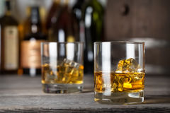 Two glasses of whiskey with ice on the bar counter. Against the bottles Stock Photo