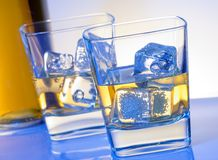 Two glasses of whiskey with ice on blue light Stock Photos
