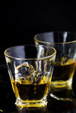 Two glasses of whiskey with ice cubes Royalty Free Stock Photos