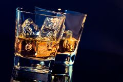 Two glasses of whiskey with ice cubes on black background with light tint blue Stock Photo