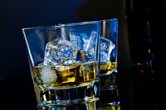 Two glasses of whiskey with ice cubes on black background with light tint blue Royalty Free Stock Photos