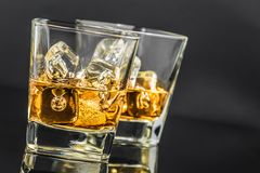 Two glasses of whiskey with ice cubes on dark background Stock Photography